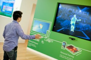 A person using the Kinect, with their silhouette shown on screen.