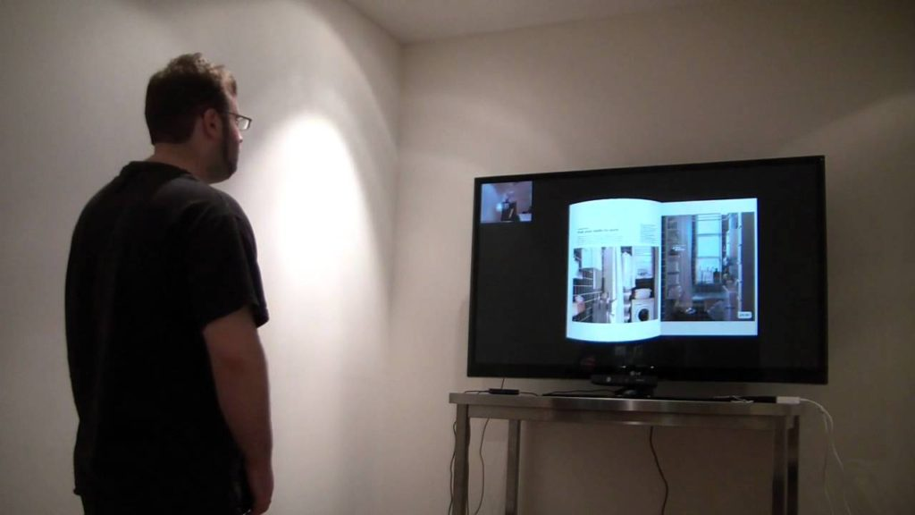 A person reading a digital book on screen using the Kinect.