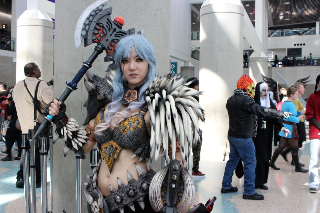 Female cosplayer wielding an axe, wearing spiky armor at LA Comic Con 2018.