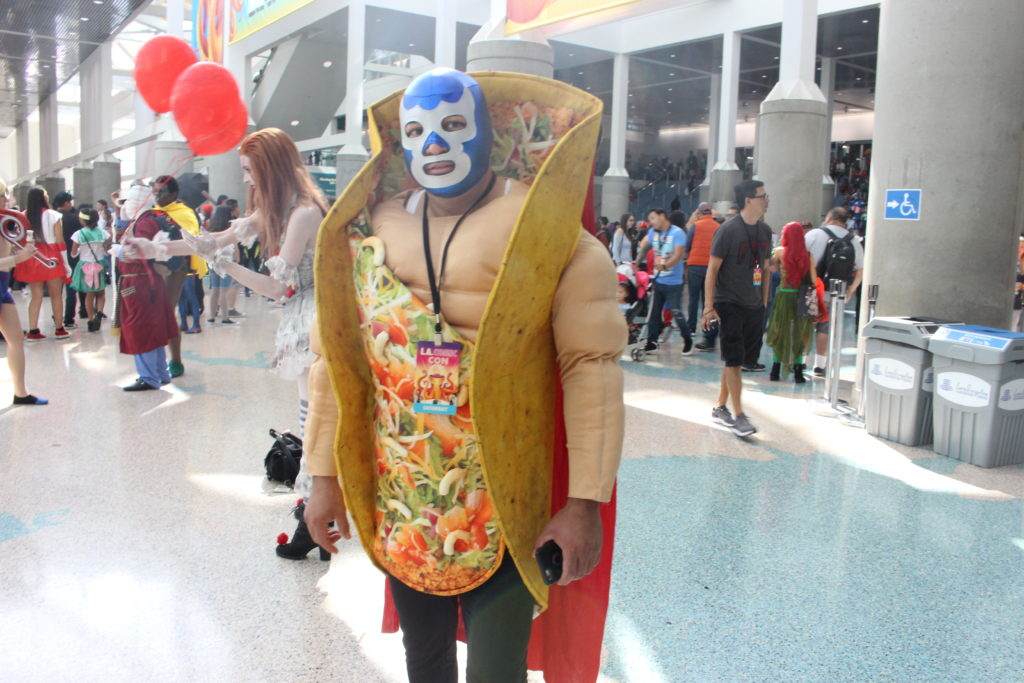 Man combines taco custome with a luchador costume.